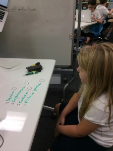 A 4th grader working through her checklist/rubric on a whiteboard table